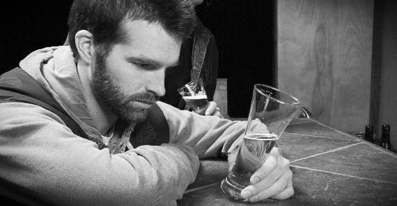 Man in Bar Staring at Beer Glass