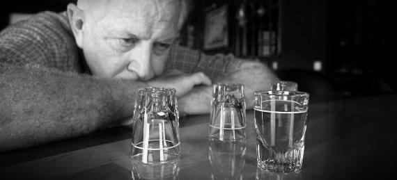 Man at Bar Staring at Full Shot Glass
