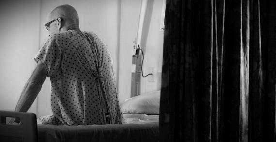 Senior Man Sitting on Edge of Hospital Bed