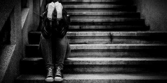 Addict Sitting on Steps With Head in Hands